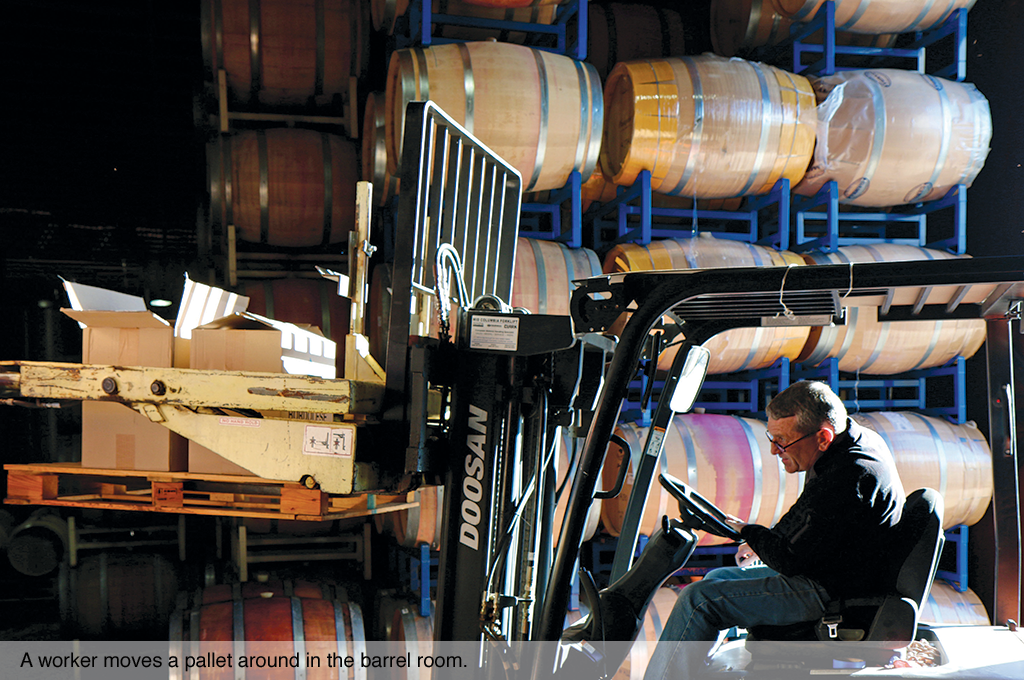 A worker moves a pallet around in the barrel room.