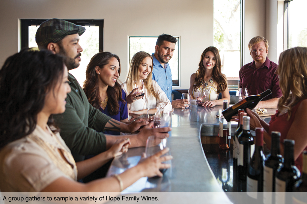 A group gathers to sample a variety of Hope Family Wines.
