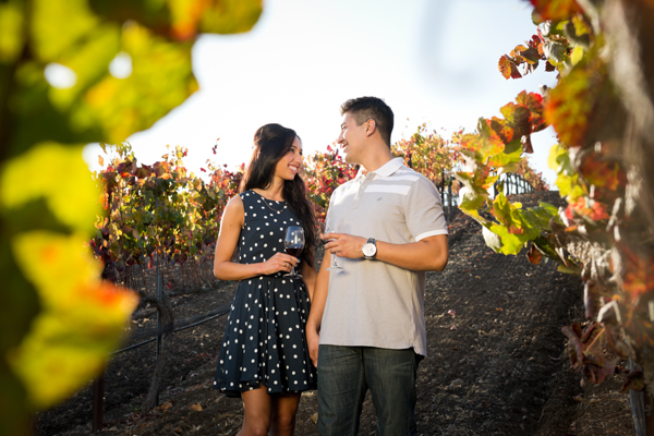 A couple enjoys a tasting in the vineyard.